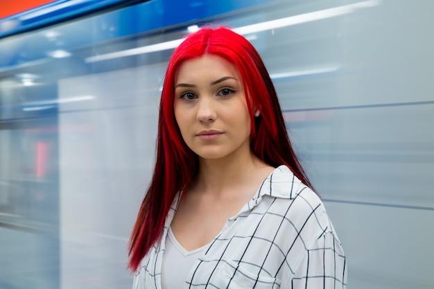 通過する電車を背景に地下鉄で美しい悲しい赤毛の10代の少女。
