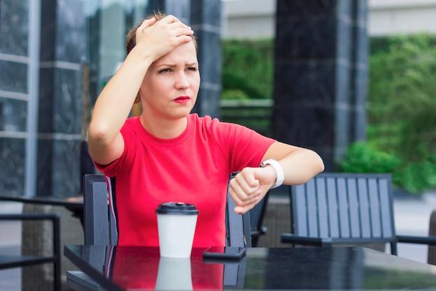 Красивая грустная расстроенная нервная девушка, держащая голову рукой, вспомнила, что забыла или забыла что-то делать. молодая женщина спешит, не успевает, смотрит на часы, проверяет время. кафе, кофе.