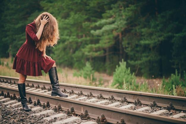 Красивая грустная женщина в малиновом платье прячет лицо волосами в лесу на железной дороге