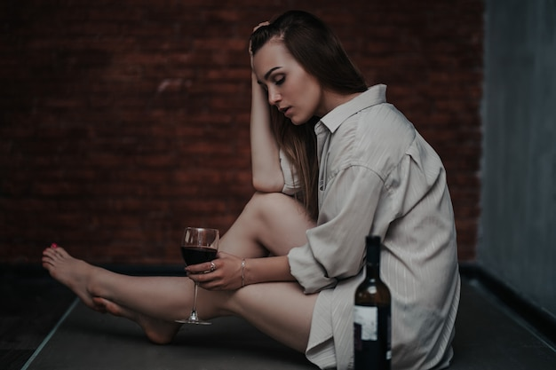 Beautiful sad woman sitting on floor in shirt, hold wine she is upset, alone, nobody loved, without love