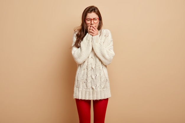 La bella donna triste soffre di dolore, ha la depressione per il dolore, copre la bocca, cerca di smettere di piangere, soffre di mal di denti, indossa un maglione bianco a maniche lunghe, ha un'espressione del viso infelice, sta al chiuso