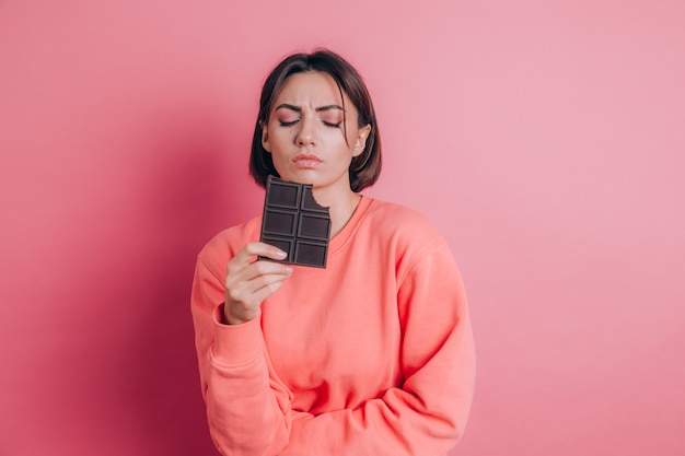 Beautiful sad woman with abdominal pain with chocolate bar on pink background and bright makeup
