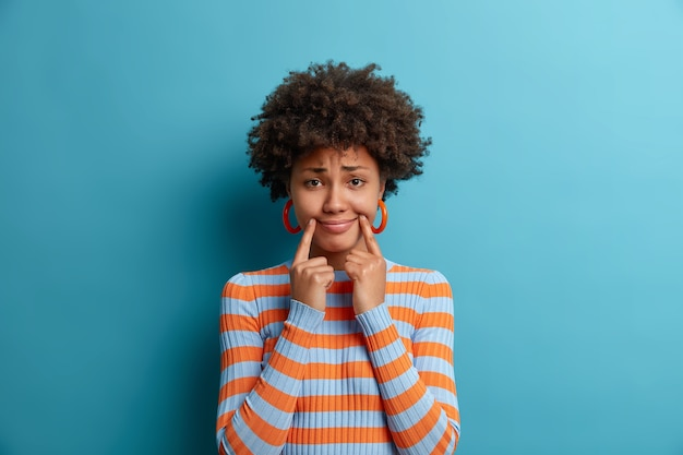 巻き毛の美しい悲しい女性は偽の笑顔を強制し、唇の端の近くで指を保持し、ボーイフリンで別れた後に落ち込んでいると感じ、失望した表情を失望させ、憂鬱に見えます