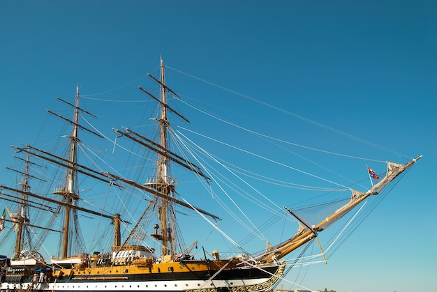 Beautiful sailing vessel with big masts on the mooring