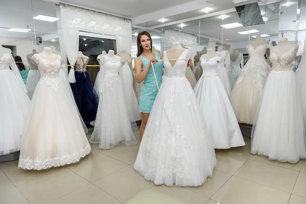Красивая продавщица, измеряющая свадебное платье на манекене