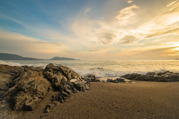 Beautiful sand beach with soft wave hit the rock and sand sea beach in the evening sunset