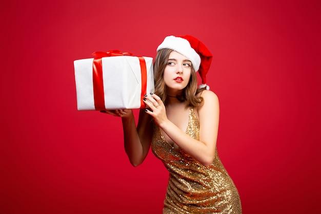 Красивая девушка санта в золотом элегантном вечернем платье и новогодней шапке с новогодним подарком в руках