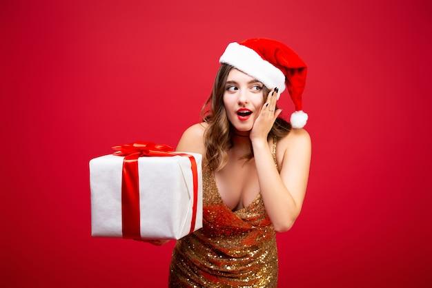 手に新年の贈り物と金のエレガントなイブニングドレスとクリスマスの帽子の美しいサンタの女の子