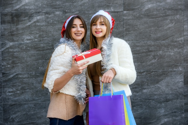 Beautiful santa girls with gift boxes, shopping bags and sparkling garland celebrating new year
