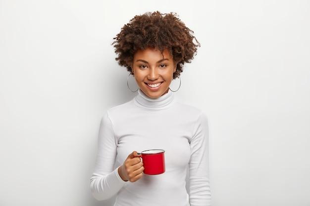 美しい満足のいく暗い肌のティーンエイジャーは、熱い飲み物で赤いマグカップを保持します