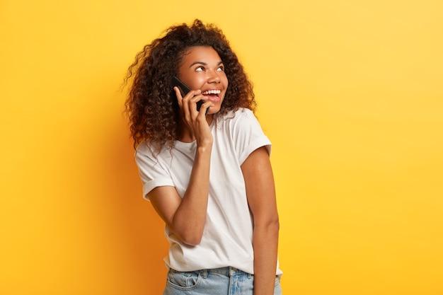 Bella giovane donna afroamericana soddisfatta gode di una piacevole conversazione, tiene il cellulare vicino all'orecchio, guarda da parte, indossa una maglietta bianca casual