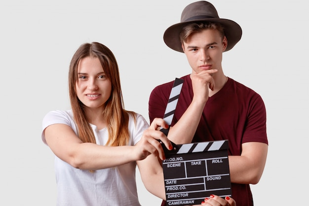 Beautiful satisfied young female holds clapperboard, signals next scene of movie, thoughtful man in hat stands in foreground, wears hat