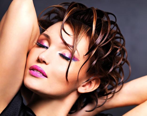 밝은 핑크 메이크업과 세련된 패션 헤어 스타일-포즈와 아름다운 saxy 여자.