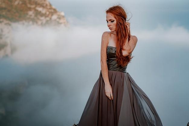 금속 사슬이 달린 회색 드레스를 입은 아름다운 스칸디나비아 전사 생강 여성