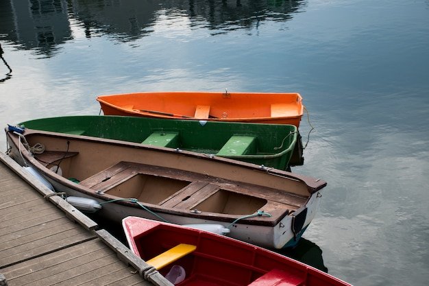 Beautiful scene of four colorful boats in next to the wooden shore of the lake