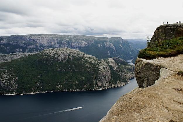 Beautiful scenery of famous preikestolen cliffs near a lake under a cloudy sky in stavanger, norway