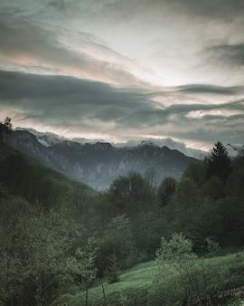 Splendido scenario di una foresta e verdi colline con montagne rocciose e nuvole incredibili