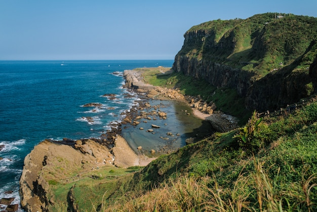 Beautiful scenery of green hills and rock formations near the sea