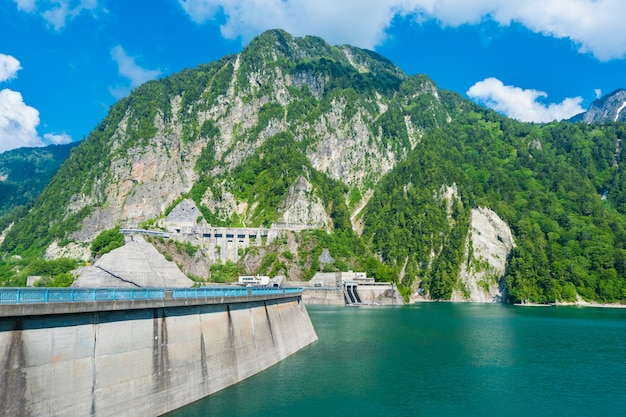 Beautiful scenery of kurobe dam on a brisk, with colorful lakeside mountains and crystal c