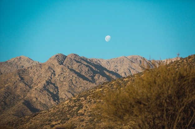 Beautiful scenery of a mountain range at sunset and the moon out