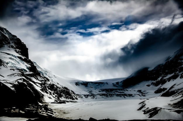 Beautiful scenery of a mountainous landscape with rocky mountains covered with snow under sunlight