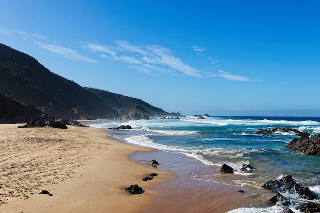 澄んだ空の下の丘に囲まれたビーチの美しい風景
