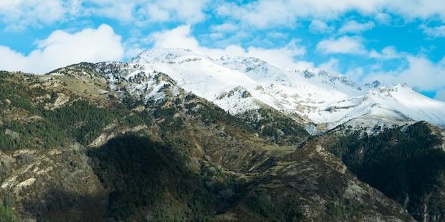 Красивые пейзажи высокого скалистого горного хребта, покрытого снегом, под пасмурным небом