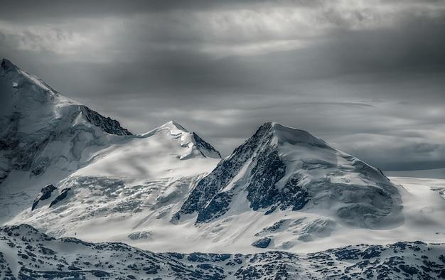 曇り空の下、雪に覆われた山並みが美しい