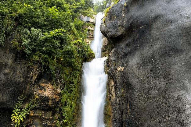 Красивые пейзажи водопада, протекающего через скалистые утесы.