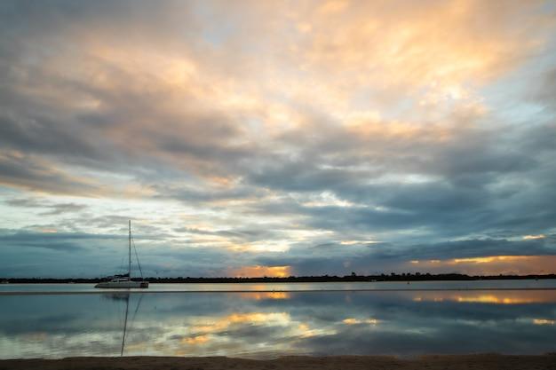 日没時に海に映る色とりどりの雲の美しい風景
