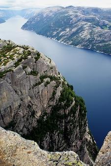 Красивые пейзажи знаменитых скал прекестулен возле озера под облачным небом в ставангере, норвегия