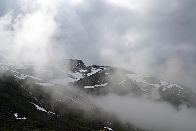 ノルウェーの霧に包まれた雪で覆われた高い岩山の美しい風景