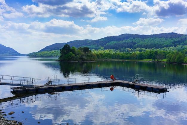 スコットランド、アーガイルアンドビュートの反射のあるローモンド湖の西岸にある集落、インバーアグラスの美しい風景