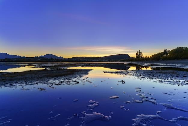 ニュージーランドの南島、ワナカ、反射のある夜明けの夕暮れのワナカ湖の美しい風景