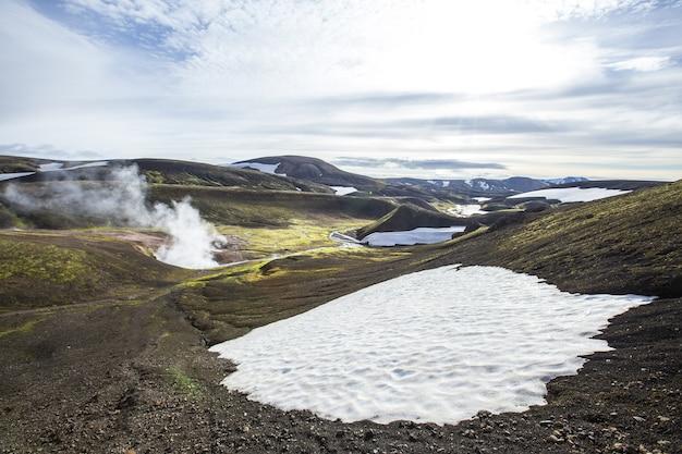 산에서 끓는 물과 눈의 웅덩이의 아름다운 풍경