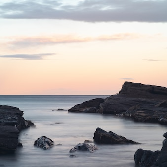息をのむようなカラフルな空の下の海の奇岩の美しい風景