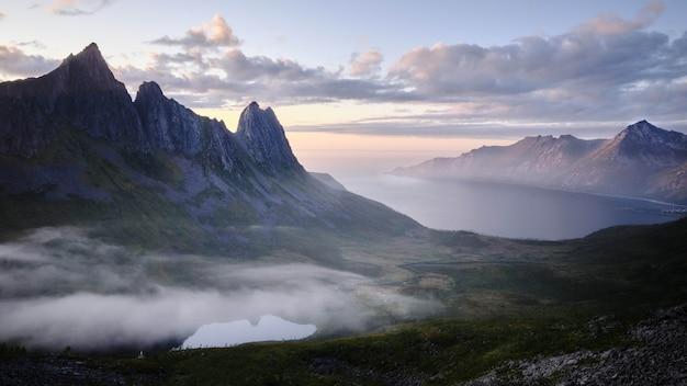 夕焼けの息を呑むような曇り空の下、海沿いの岩の崖の美しい風景