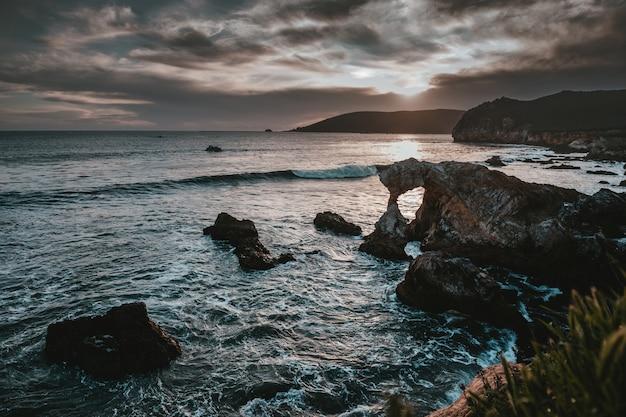 절벽, 암초, 바위 및 하늘의 숨막히는 구름이있는 바다의 아름다운 풍경