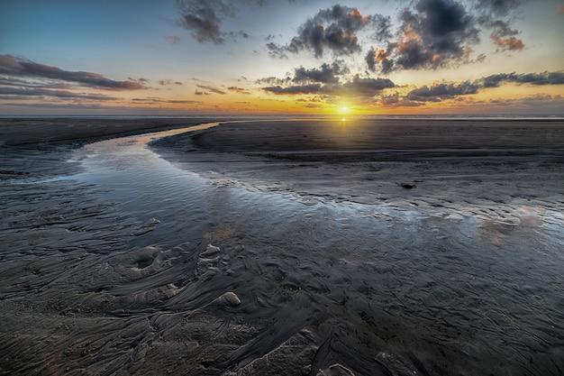 曇り空の下の干潟に映る夕日の美しい風景