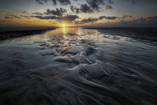 일몰의 아름다운 풍경은 흐린 하늘 아래 갯벌에 반영