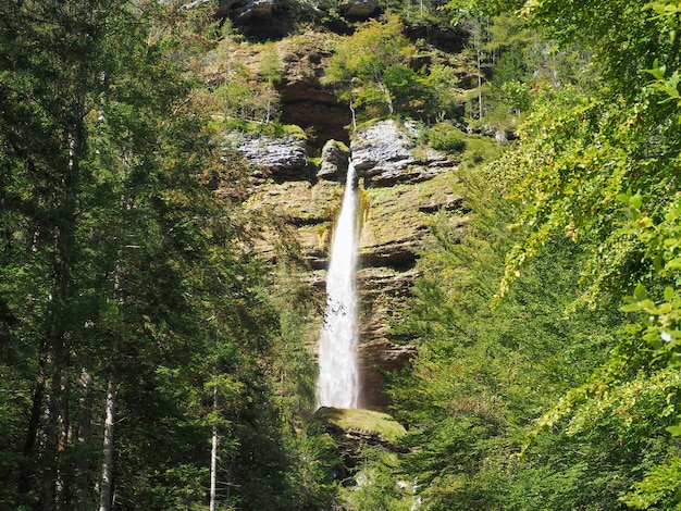 Красивый пейзаж водопада, который проходит через скалы, покрытые мхом в лесу.
