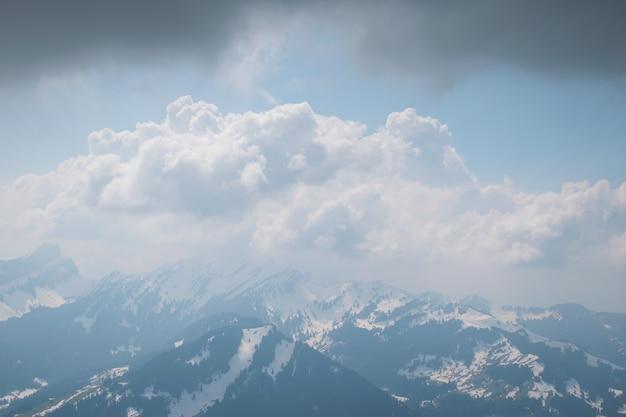 Красивые пейзажи белых облаков, покрывающих хребет высоких скалистых гор.
