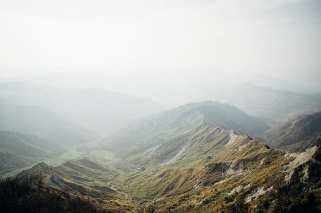Uno splendido scenario di una catena di montagne verdi avvolte nella nebbia