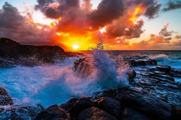 Splendido scenario di formazioni rocciose in riva al mare a queens bath, kauai, hawaii al tramonto