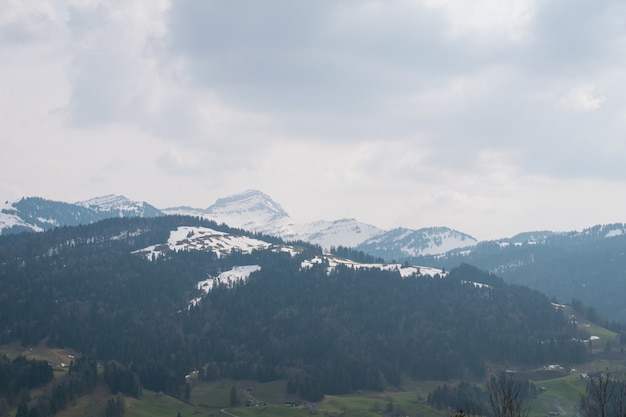 Beautiful scenery of rocky mountains covered with snow under the cloudy sky in france
