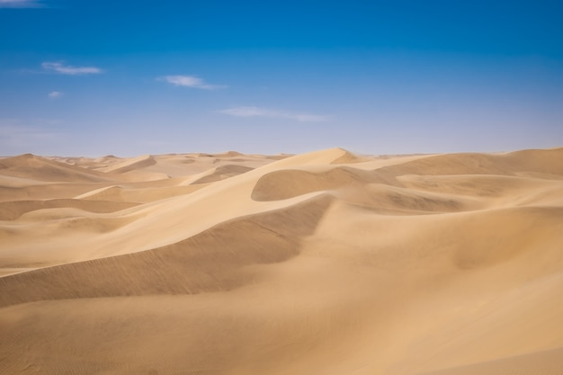 Beautiful scenery of sand dunes in a desert on a sunny day