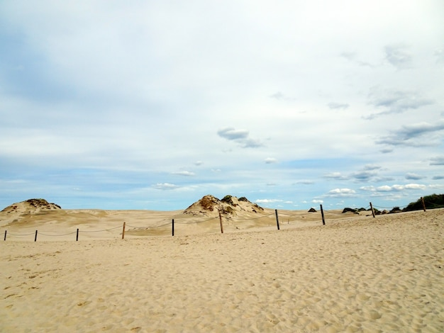 Beautiful scenery of a sandy beach under a cloudy sky in leba, poland