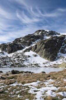 Bellissimo scenario di un paesaggio innevato con scogliere rocciose sotto un cielo nuvoloso