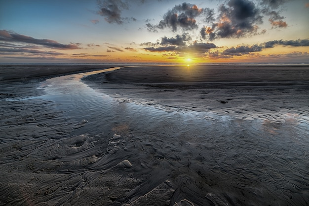 Beautiful scenery of the sunset reflected in a mudflat under the cloudy sky