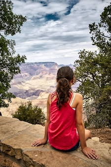 Beautiful scenery of a young girl sitting in grand canyon national park, arizona - usa